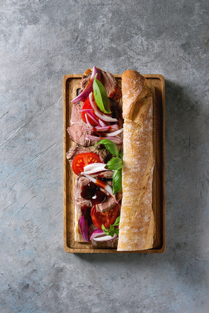 Beef baguette sandwich with tomatoes, basil, red onion served on wooden serving board over grey texture background. Flat lay, space Stock fotó