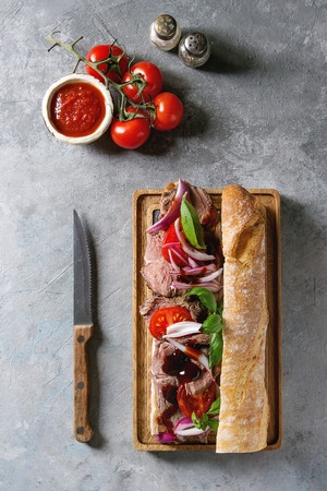 Beef baguette sandwich with tomatoes, basil, red onion served on wooden serving board with ingredients above over grey texture background. Flat lay, space
