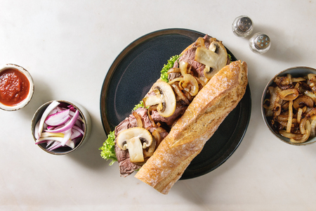 Beef baguette sandwich with champignon mushrooms, green salad, fried onion served on ceramic plate with ingredients above over white marble background. Flat lay, space Stock fotó