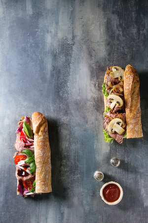 Two Beef baguette sandwiches with champignon mushrooms, green salad, fried onion, tomatoes, salt and sauce over blue texture background. Flat lay, space Banque d'images - 118585700