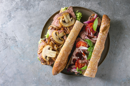 Variety of beef baguette sandwich with champignon mushrooms, green salad, tomatoes, fried onion served on ceramic plate over grey texture background. Flat lay, space Stock fotó