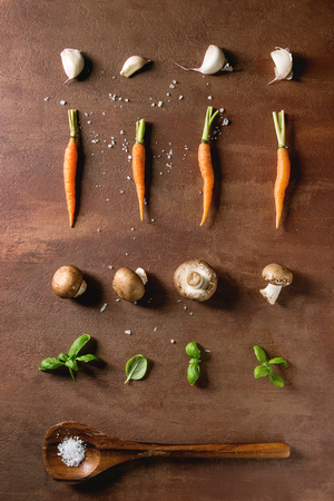 Fresh basil herbs with mini carrots and champignon mushrooms in row, wooden spoon with salt over brown background. Flat lay, space. Cooking concept, food background.