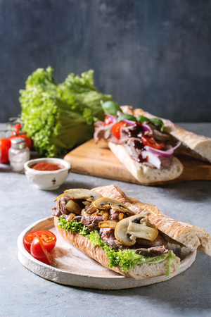 Beef baguette sandwich with champignon mushrooms, green salad, fried onion served on ceramic plate with ingredients above over grey blue table.