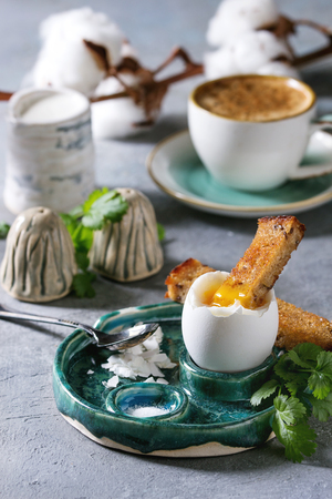 Breakfast with cup of coffee and soft boiled egg, served in green ceramic egg cup with salt, pepper and toasted bread, jug of cream and cotton flowers over grey blue table. Archivio Fotografico - 118585810