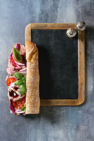 Beef baguette sandwich with tomatoes, basil, red onion served on empty black chalkboard with salt and pepper over blue texture background. Flat lay, space Banque d'images - 118585824