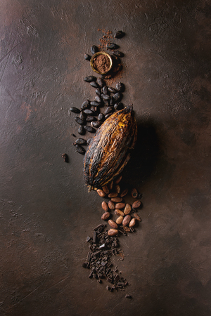 Variety of fresh and dry cocoa beans and cocoa pod with chopped dark chocolate and cocoa powder over brown texture background. Flat lay, space Archivio Fotografico