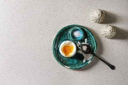 Breakfast with soft boiled egg, served in green ceramic egg cup with salt and pepper over grey spotted table. Archivio Fotografico - 118587119