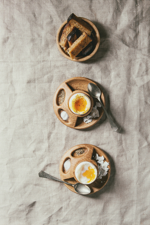 Breakfast with soft boiled eggs, served in wooden egg cup with salt, pepper and toasted bread in row over linen tablecloth. Flat lay, space Stock Photo
