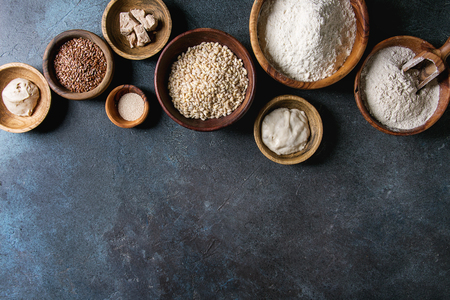 Ingredients for baking bread. Variety of wheat and rye flour, grains, yeast, sourdough over dark blue texture background. Flat lay, space Standard-Bild