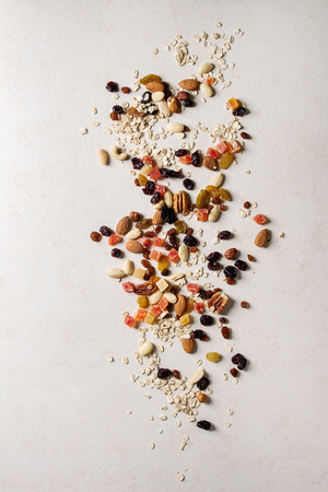 Variety of dried fruits, nuts and oat flakes for cooking homemade healthy breakfast muesli or granola energy bars over white texture background. Flat lay, space.