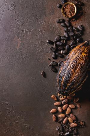 Vielzahl von frischen und trockenen Kakaobohnen und Kakaoschote mit gehackter dunkler Schokolade und Kakaopulver auf braunem Texturhintergrund. Flache Lage, Raum