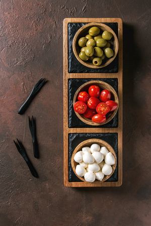 Mozzarella, cherry tomatoes, olives antipasto appetizers served in wooden bowl on slate serving board over brown texture background. Flat lay, space Stock Photo