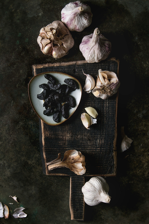 Variety of fresh organic garlic bulbs whole and peeled and cloves of black fermented garlic on wooden chopping board over dark metal background. Flat lay, space Banco de Imagens