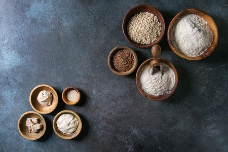 Ingredients for baking bread. Variety of wheat and rye flour, grains, yeast, sourdough over dark blue texture background. Flat lay, space Stock Photo