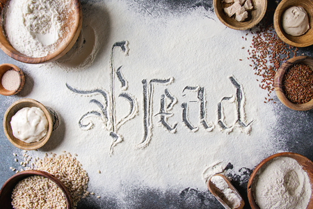 Ingredients for baking bread. Variety of wheat and rye flour, grains, yeast, sourdough, gothic calligraphy handwritten lettering bread sifted flour over blue background. Flat lay