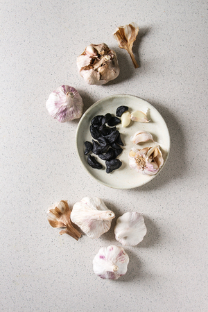 Variety of fresh organic garlic bulbs whole and peeled and cloves of black fermented garlic in ceramic plate over grey spotted background. Flat lay, space