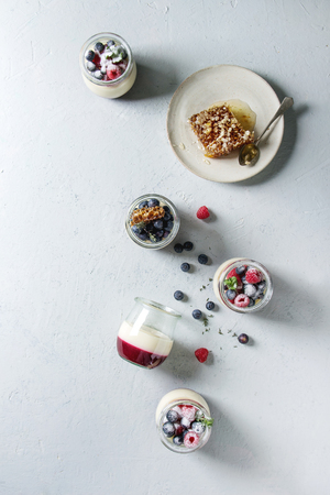 Homemade classic dessert Panna cotta with raspberry and blueberry berries and jelly in jars, decorated by mint, sugar powder, honey combs over grey texture background. Flat lay, space
