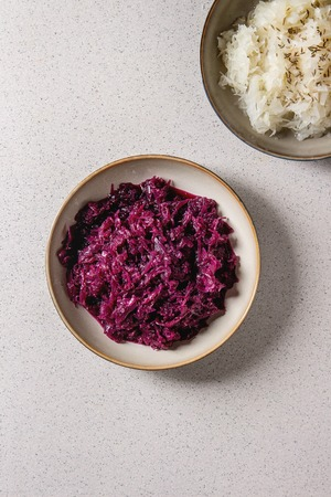 Red and white sauerkraut chopped cabbage pickled in brine with cumin in ceramic plate over grey spotted background. Flat lay, space