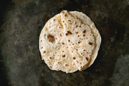 Homemade pita or chapati flatbread flapjack over dark metal background. Flat lay, space Stock Photo