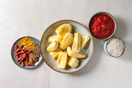 Ingredients for cooking vegan curry. Ripe raw peeled jackfruit with white uncooked rice, chopped tomatoes and spices in ceramic bowls over white marble background. Flat lay, space