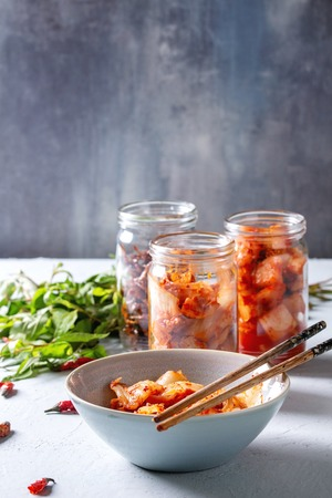 Korean traditional fermented appetizer kimchi cabbage and radish salad, hot spicy anchovies fish snack served in glass jars and bowl with Vietnamese oregano and chili peppers over grey blue table. 스톡 콘텐츠