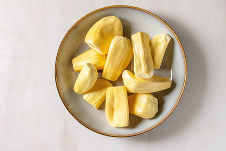 Ripe raw peeled jackfruit in ceramic plate over white marble background. Flat lay, space
