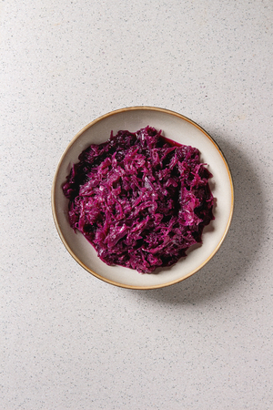 Red sauerkraut chopped cabbage pickled in brine with cumin in ceramic plate over grey spotted background. Flat lay, space