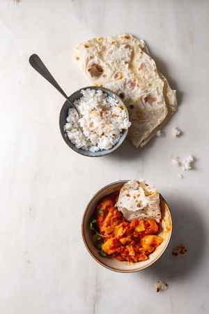 Started eaten Vegan vegetarian curry with ripe yellow jackfruit served in ceramic bowl with rice, coriander and homemade flatbread flapjack over white marble background. Flat lay, space
