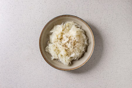 White sauerkraut chopped cabbage pickled in brine with cumin in ceramic plate over grey spotted background. Flat lay, space