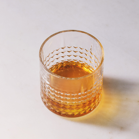 Glass of scotch whiskey standing on white marble background. Alcohol drink. Square image