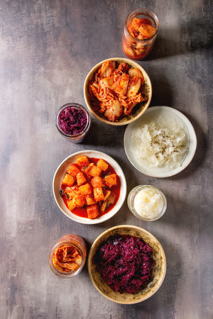 Variety of fermented food korean traditional kimchi cabbage and radish salad, white and red sauerkraut in glass jars and ceramic plates over grey texture background. Flat lay, space 스톡 콘텐츠