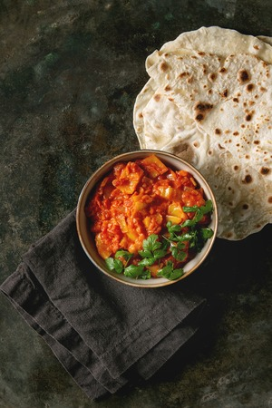 Vegan vegetarian curry with ripe yellow jackfruit served in ceramic bowl with coriander and homemade flatbread flapjack over dark metal background. Flat lay, space