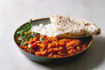 Vegan vegetarian curry with ripe yellow jackfruit served in ceramic bowl with rice, coriander and homemade flatbread flapjack over white marble table. Stock Photo