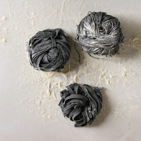 Variety of italian homemade raw uncooked cuttlefish ink black pasta spaghetti and tagliatelle with semolina flour over white marble background. Flat lay, space. Square image