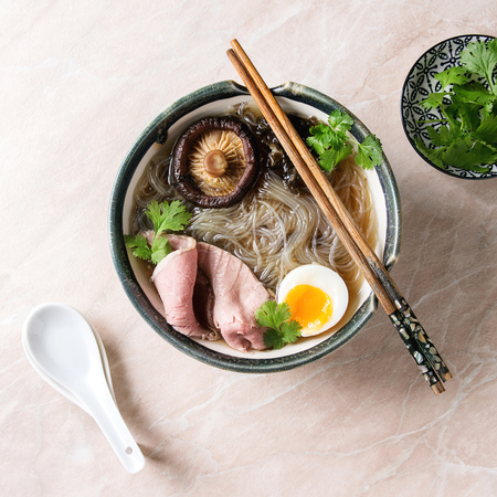 Traditional Japanese Noodle Soup with shiitake mushroom, egg, sliced beef and greens served in ceramic bowl with wooden chopsticks and white spoon over pink marble background. Flat lay, space. Square image