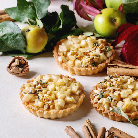 Homemade sweet apple shortbread tartlets with cinnamon sticks, walnuts, apples red leaves branches above on white marble table. Autumn baking. Square image