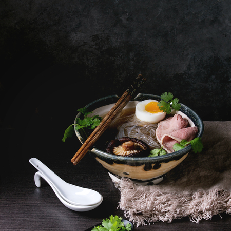 Traditional Japanese Noodle Soup with shiitake mushroom, egg, sliced beef and greens served in ceramic bowl with wooden chopsticks and white spoon on cloth over dark table. Asian style dinner. Square image
