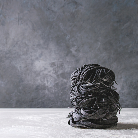 Variety of italian homemade raw uncooked cuttlefish ink black pasta spaghetti and tagliatelle in stack with semolina flour on white marble table. Copy space. Square image