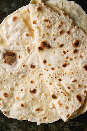 Homemade pita or chapati flatbread flapjack over dark metal background. Flat lay, close up