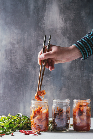 Korean traditional fermented appetizer kimchi cabbage and radish salad, fish snack served in glass jars with Vietnamese oregano and chili peppers over grey blue table. Chopsticks in mans hands.