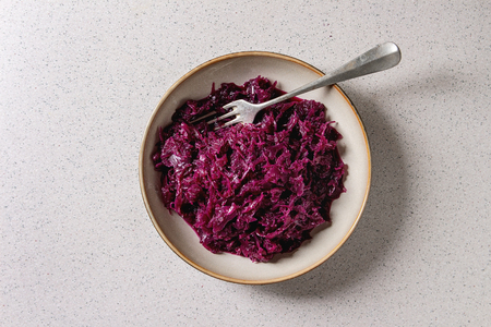 Red sauerkraut chopped cabbage pickled in brine with cumin in ceramic plate with fork over grey spotted background. Flat lay, space