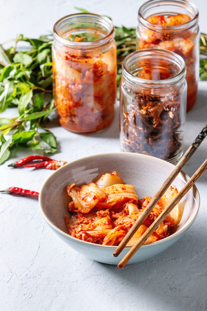 Korean traditional fermented appetizer kimchi cabbage and radish salad, hot spicy anchovies fish snack served in glass jars and bowl with Vietnamese oregano and chili peppers over grey blue table. Stock Photo