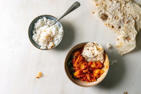 Started eaten Vegan vegetarian curry with ripe yellow jackfruit served in ceramic bowl with rice, coriander and homemade flatbread flapjack over white marble background. Flat lay, space Standard-Bild - 119351795