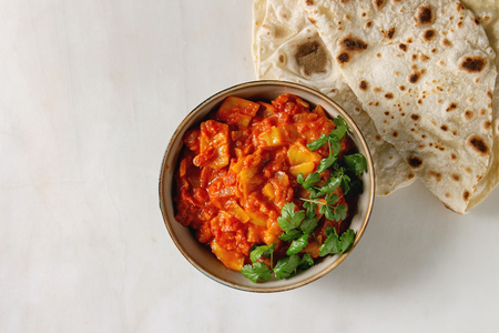 Vegan vegetarian curry with ripe yellow jackfruit served in ceramic bowl with coriander and homemade flatbread flapjack over white marble background. Flat lay, space