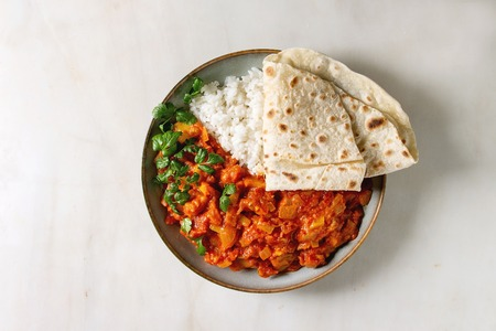 Vegan vegetarian curry with ripe yellow jackfruit served in ceramic bowl with rice, coriander and homemade flatbread flapjack over white marble background. Flat lay, space Stock Photo