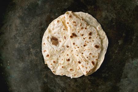 Homemade pita or chapati flatbread flapjack over dark metal background. Flat lay, space Stock Photo