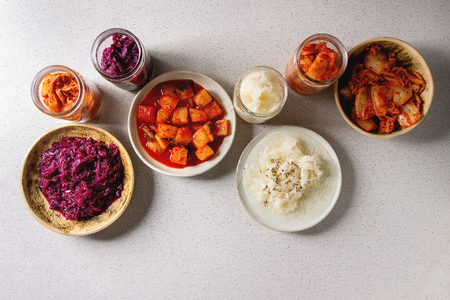 Variety of fermented food korean traditional kimchi cabbage and radish salad, white and red sauerkraut in glass jars and ceramic plates over grey spotted background. Flat lay, space