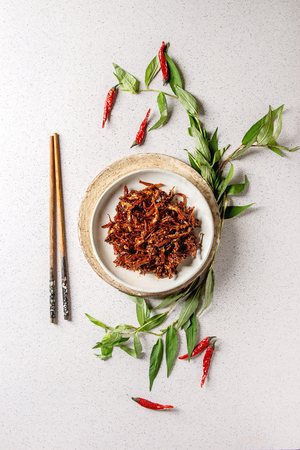 Vietnamese traditional hot spicy anchovies fish snack in ceramic plates with Vietnamese oregano greens and chopsticks over grey spotted background. Flat lay, space.