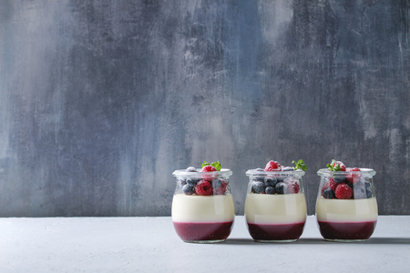 Homemade classic dessert Panna cotta with raspberry and blueberry berries and jelly in jars, decorated by mint and sugar powder over white blue table
