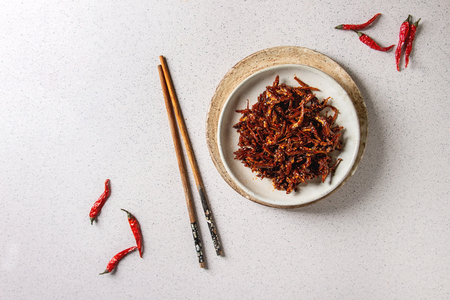 Vietnamese traditional hot spicy anchovies fish snack in ceramic plates with chopsticks over grey spotted background. Flat lay, space.